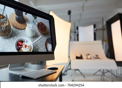 Interior of spacious photostudio: modern computer with colorful picture on foreground, professional equipment on background