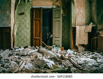 Interior of spooky abandoned dilapidated house with torn wallpaper and smashed household objects