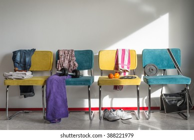 Interior sports and gym concept. Sneakers, dumbbell, bag, jeans and towels on chairs in sunny locker room.