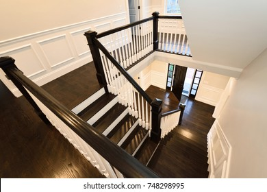 Interior staircase in new home. Colonial style, dark hardwood floor.