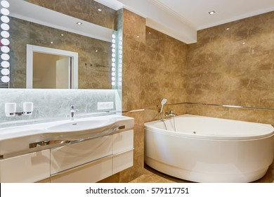 Interior of stylish bathroom in brown and white colors, with rounded ceramic bath in corner of the room and big mirror on wall and light around. White commode and accessories for bath.