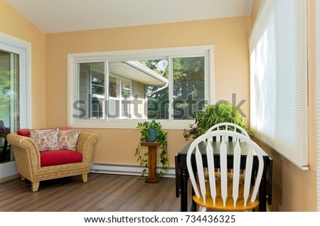 interior of sunroom addition to home and decor including small table with chairs and view of home exterior from window