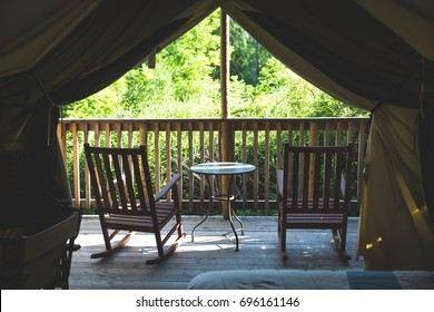 Interior of tent cabin in the woods with two chairs and table on deck