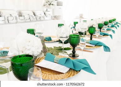Interior of tent for wedding diner, ready for guests. Served round banquet table outdoor in marquee decorated hydrangea flowers, Golden dishes and green napkins. Catering concept