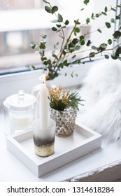 Interior tray decoration with burning candle, mimosa flowers and branches