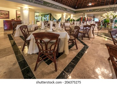 Interior of the tropical, caribbean restaurant with nicely served and decorated tables of the luxury resort.
