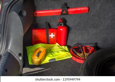 The interior of the trunk of the car in which there is a first aid kit, fire extinguisher, warning triangle, reflective vest, starter cables and tow rope.