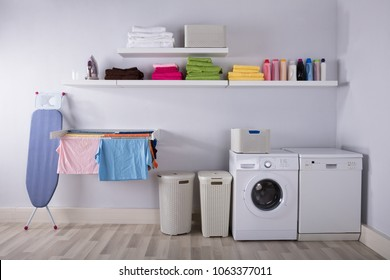 Interior Of Utility Room With Washing Machine And Drying Clothes