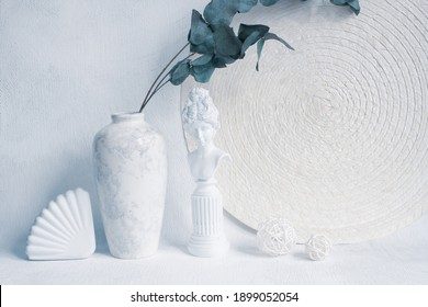 Interior vertical still life in pastel colors. Minimalist trendy style. Comfort and harmony in home design and decor. Decorative plaster trinkets, napkin, vase with eucalyptus leaves.