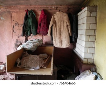 The interior of a very poor, dilapidated home. Abandoned apartment after war. Clothes, tile stove, trash. Poor people, refugees.