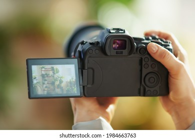 Interior videography. Closeup on modern woman with mirrorless camera at modern home in sunny day.