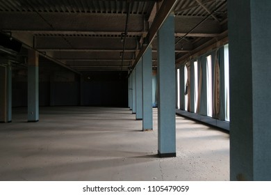 Interior view of an abandoned building with several columns. Natural light.