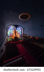 An interior view of an abandoned Hebrew Jewish synagogue bathed in blue hues and affixed with a beautiful stained glass window in New York.