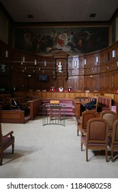Interior view of the assize court of Montpellier city, located in the courthouse, France. September, 16, 2018. Large painting, screen, bright wooden decorative walls, old chairs and desks visible.