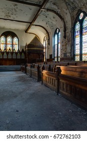 An interior view of a beautiful chapel with stained glass and wood pews at an abandoned boys school in New York.