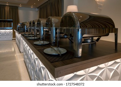 Interior view of a catering room buffet party ready to welcome people for a wedding or celebration event. Chafing dish. Plates and kitchen tongs in front of them for the guests to serve themselves