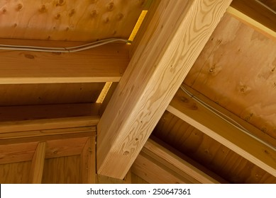 The interior view of the construction of a pitched roof showing the ridge, rafters and sheathing. Horizontal shot.
