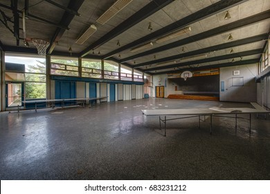 An interior view of a derelict circa 1962 cafeteria, stage and gymnasium at an abandoned school.