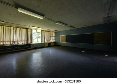 An interior view of a derelict classroom with brown curtains and chalkboard at an abandoned school.