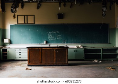 An interior view of a derelict classroom with a center wood table and chalkboard at an abandoned school.