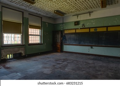 An interior view of a derelict classroom with a chalkboard and windows at an abandoned school.