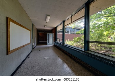 An interior view of a derelict hallway with large picture windows at an abandoned school.