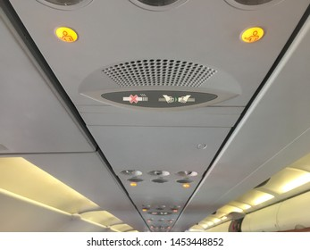 Interior view down the length of aeroplane cabin ceiling showing call buttons and no smoking and fasten seat belt signs.Internal lights running down each side are on also air vents can be seen - Image