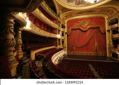 Interior view of the Italian-style opera house of Montpellier city, called the Opéra Comédie, in France. September, 16, 2018. Red and gold rows, balconies, seats and curtain. Design with curved shapes