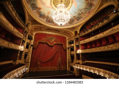 Interior view of the comédie opéra, located in the center of Montpellier city, France. September, 16, 2018. Large circular luminary fixed at the painted ceiling. Wooden golden balconies and red seats.