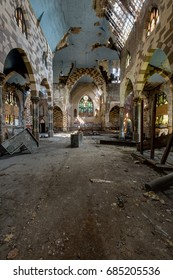 An interior view of a long abandoned church with broken stained glass windows, a collapsing wood floor, a deteriorating ceiling and the remains of painted plaster.