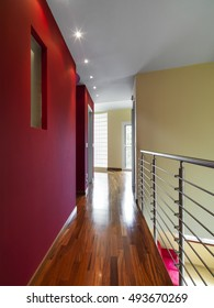 interior view of a modern apartment in foreground the corridor whose floor is made of wood and the wall is colored of purple