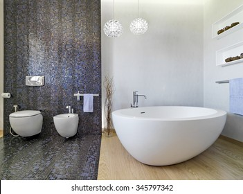 interior view of a modern bathroom in foreground the bathtub and sanitay.ware, the floor is made of wood and mosaic tiles.