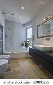 interior view of a modern bathroom whose flooring is made of  wood  overlooking on the bathtub