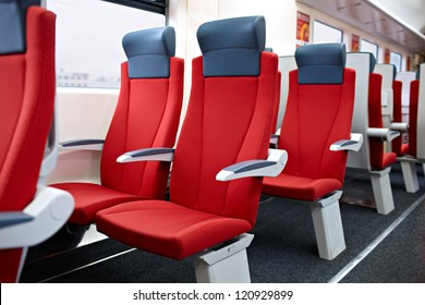 An interior view of  a modern high speed train. Red chairs.