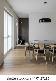 interior view of a modern living room whose floor is made of wood in foreground the dining table and black chandelier