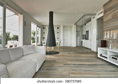 interior view of a modern living room in foreground the fabric sofa and iron fireplace