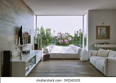 interior view of a modern living room overlooking on the terrace with white fabric couch and wooden flooring