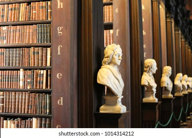 Interior view of the old library in Dublin Trinity college Ireland. Many high wooden bookshelves. Decoration with white busts. Pattern of old brown orderly books. Picture taken on 7th august 2016.