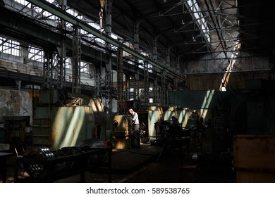 Interior view of an old locomotive factory with a ray of sun shining on the machinery