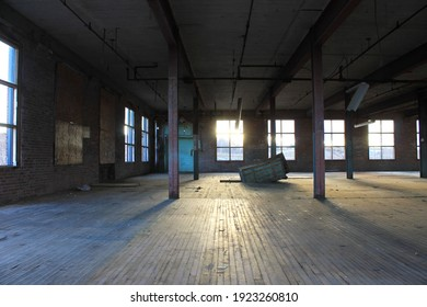 Interior view of an old, run-down, and abandoned factory building. Big, empty room with brick walls, exposed beams, and florescent light fixtures hanging form the ceiling.