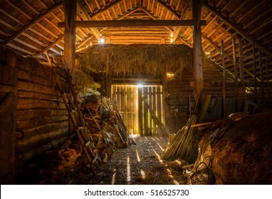interior view of the old rural barn full of hay, firewood, tools and trash