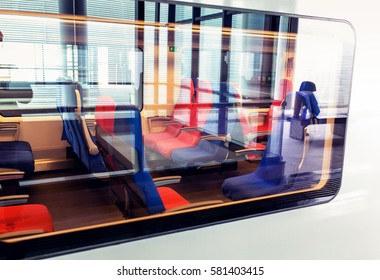 An interior view through a glass of a modern high speed train with empty seats