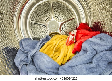 Interior view of tumble dryer with drying clothes. Conceptual image of housework and doing laundry.