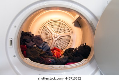 Interior view of typical modern domestic tumble dryer with laundry in it.