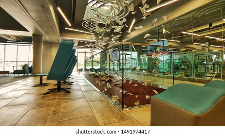 An interior view of the Wichita Public Library (second floor) in Wichita Kansas, United States, August 30, 2019: There is a sitting area with green chairs, surrounding an Art Design hanging from the c
