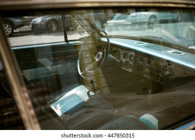The interior of a vintage classic muscle car, subdued tones