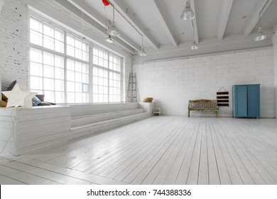 Interior with vintage furniture, light studio with old bench and blue case. Spacious studio with a high ceiling and a big window for photo shooting. Natural light