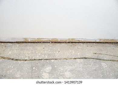 a interior wall with the baseboard removed and a bare concrete floor during a renovation