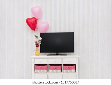 Interior wall with cabinet, tv, flowers and balloons centered in frame.