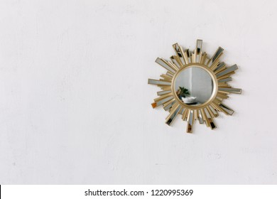 Interior wall mirror in the shape of a sun with metal brass sun rays as the frame isolated on white rustic wall background.